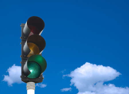 Traffic lights - green light is on - in front of blue sky photo
