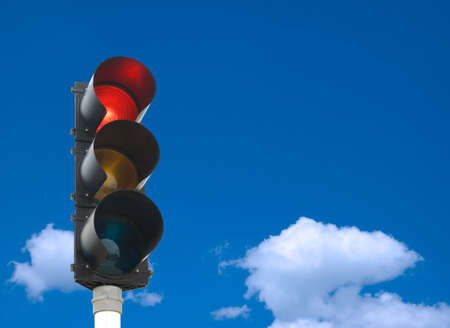 Traffic lights - red light is on - in front of blue sky photo