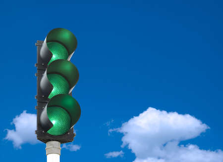 Traffic lights - all three lights are green in front of blue sky photo