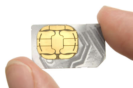 Man holding a sim-card between his thumb and index finger - closeup on sim-card, fingers are out of depth of field