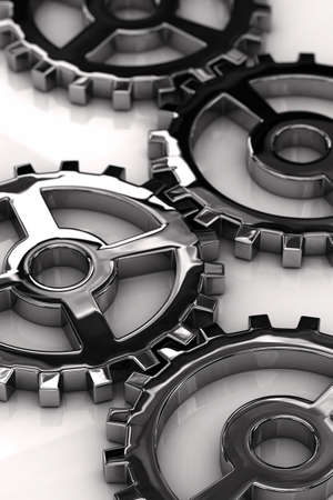 Chrome gear wheels with shallow depth of field over white glossy surface Stock Photo