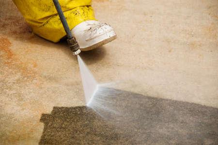 Onderhoud werknemer reiniging oud vuil oprit met een druk reiniger