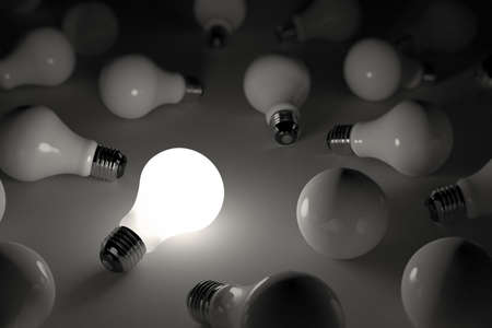 conceptual bulb: One lit light bulb amongst other broken light bulbs Stock Photo