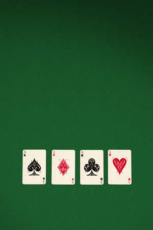 Four aces spread out on green felt background photo