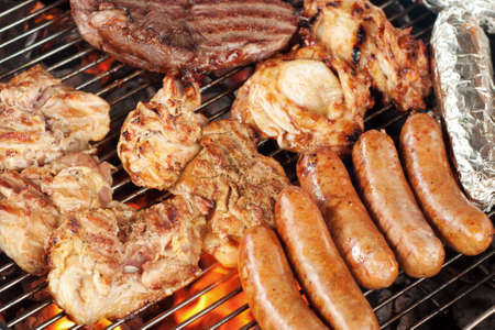 Various meats like chicken, sausage, steak and corn wrapped in aluminum foil on a barbecue grill photo