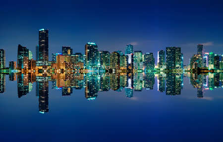 ほとんどない雲とほぼ完璧な反射と夜にマイアミのスカイライン