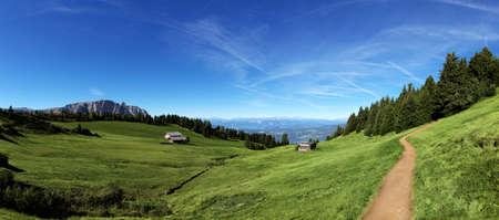 Italiaanse bergpanorama in Tirol met chalet en groene weilanden op een zonnige dag Stockfoto