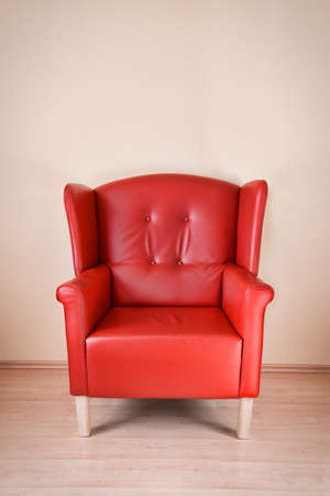arm chair: Red leather armchair against the wall on wooden floor Stock Photo