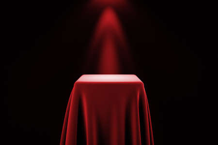 show off: Presentation pedestal covered with a red silk cloth in front of a wall illuminated by a spot light Stock Photo