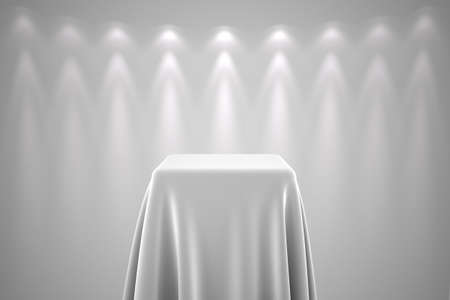 reveal: Presentation pedestal covered with a white  silk cloth in front of a wall illuminated by a spot light