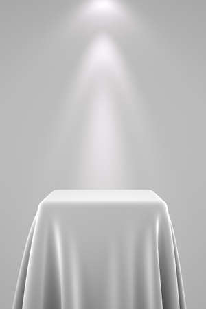 Presentation pedestal covered with a white silk cloth in front of a wall illuminated by a spot light