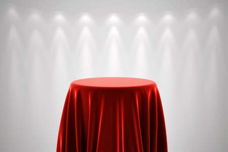 podium: Round presentation pedestal covered with a red silk cloth in front of a white wall illuminated by a spot light