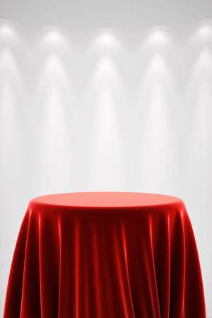 Ronde presentatie voetstuk bedekt met een rode zijden doek in de voorkant van een witte muur verlicht door een spot light