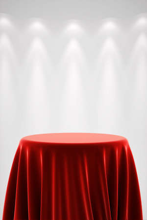 Round presentation pedestal covered with a red silk cloth in front of a white wall illuminated by a spot light