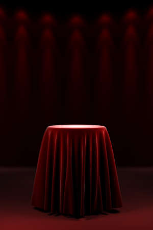 reveal: Round presentation pedestal covered with a red silk cloth in front of a wall illuminated by spot lights