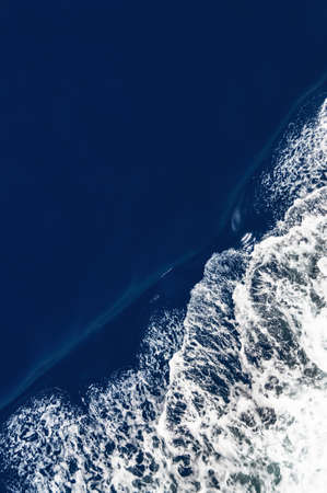 ocean wave: Birds eye view of a bow wave with slight motion blur and dark ocean surface.