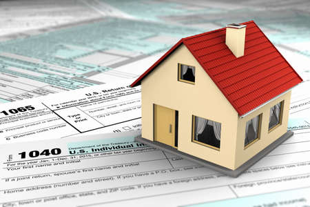impuestos: EE.UU. formularios de impuestos y una casa en miniatura que simboliza los ahorros o costos de poseer bienes inmuebles