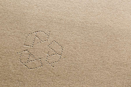 Highly detailed photograph of cardboard with the shape of the recycling symbol punched into the carton material. Foto de archivo