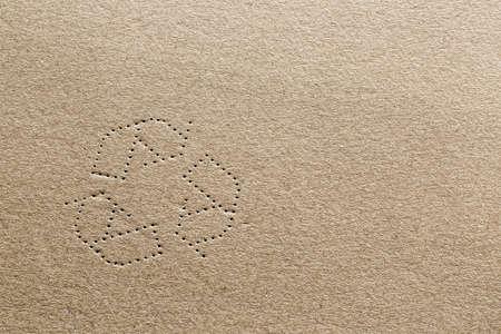 Zeer gedetailleerde foto van karton met de vorm van de recycling symbool geslagen in de doos materiaal. Stockfoto