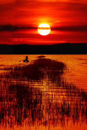 colorful water surface: Sunset on the lake fishing