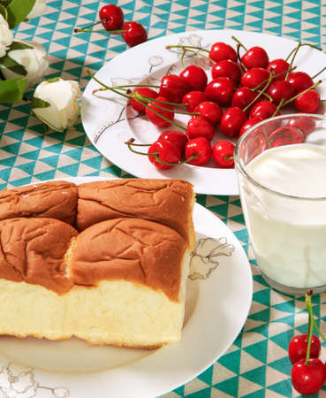 A hearty breakfast contain of bread , cherries and a cup of milk Stock Photo