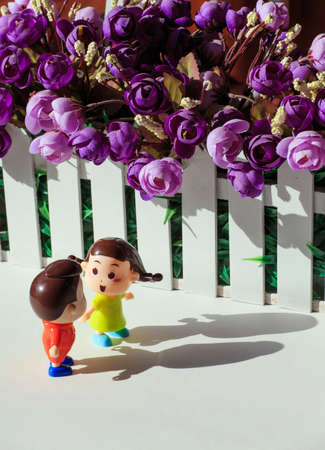 Two dolls at the edge of the flower bed