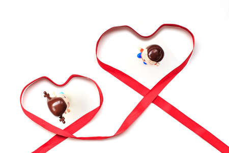 Mini figurine in a heart shape ribbon on white background