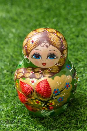 Russian doll on green grass