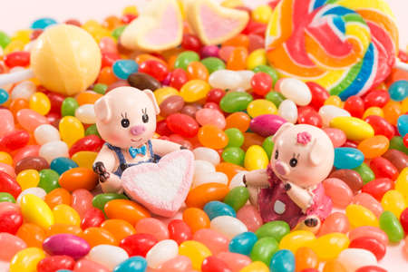 Ein Paar Schweinchenpuppen mit Süßigkeiten-Hintergrund