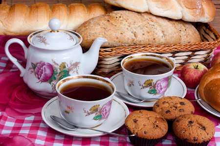 coffeecup: Two cups of tea and a kettle on the background of bread and mafin