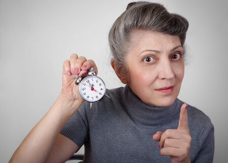 hectic life: Portrait of an elderly woman holding a clock concept of time is running out Stock Photo