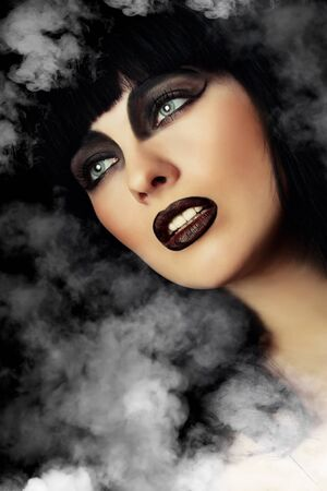 Portrait of a beautiful woman with dark make-up in a smoke Фото со стока