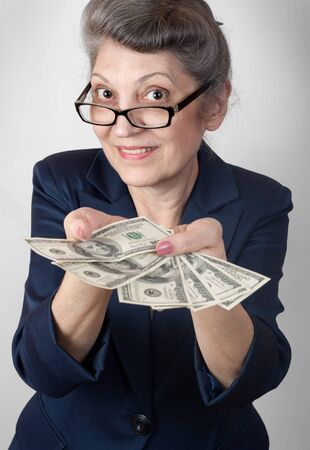 pension cuts: Portrait super happy excited successful senior woman lady holding money dollar bills in hand
