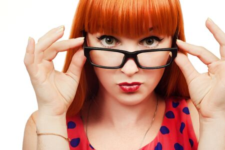 geeky: Pin-up 50s style red-haired girl in glasses on white background Stock Photo