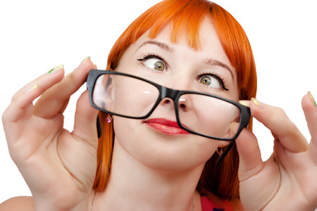 funny glasses: Funny red-haired girl in glasses grimaces on a white background