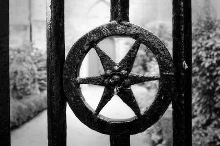 christian halloween: A star shaped detail of a cast iron gate in front of a ancient church Stock Photo