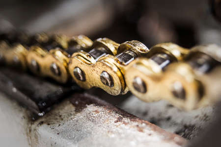 fairly: Close-up of a gold colored fairly new motorcycle chain on a bike covered with shiny oil