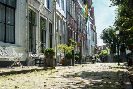 dickens: The sun is shining on this historical authentic street with old architecture and cozy benches in front of the houses.