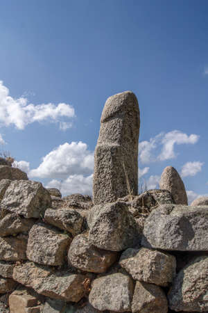 A stone phallus statue made from rock standing on a wall. The statue dates from the Neolithic period and is located in Corsica, France