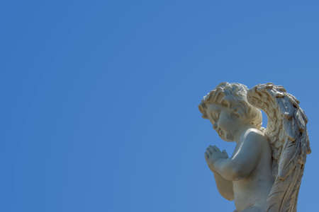 praying angel: Close-up of a marble statue of an white praying Angel child with a blue sky and plenty of space for text