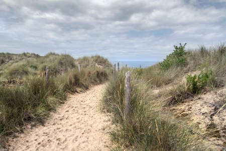 A sandy trail leading to a sunny beach in France, overseeing the ocean and blue sky