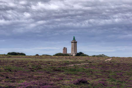 A large lighthouse building on a high hill covered with heather at the beach of France