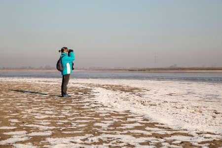 dutch girl: Woman looking through binoculars in a winter landscape