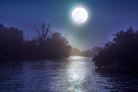 Ein fließender Fluss im Donau-Delta in Rumänien bis zum Nacht mit einem Vollmond, der im Wasser sich reflektiert Standard-Bild - 74556805