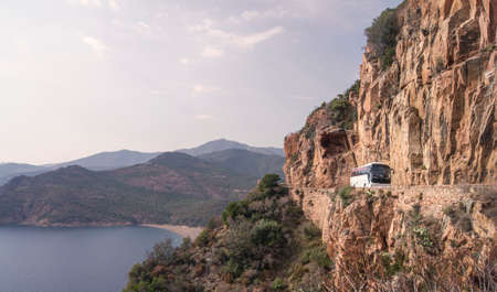 water bus: A white tourist bus on a Mediterranean mountain road on a cliff of a sunny bay