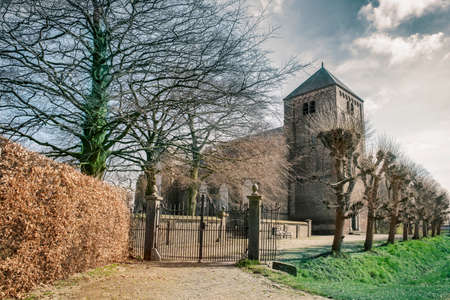 A beautiful image of an old and historical church with early gothic bell tower and cast iron gate in front of it.