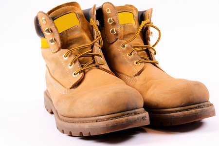 Dirty working boots isolated on white photo