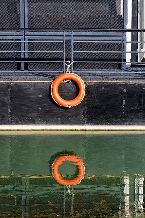 Red buoy on ship with reflection in water photo