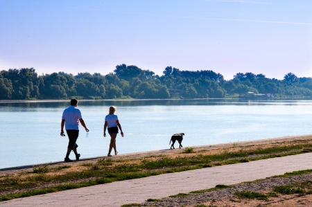 Couple have dog walking by the water photo