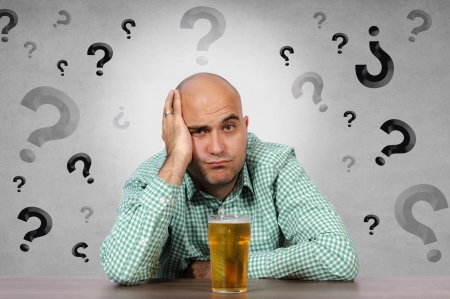 Man hesitating whether to drink beer photo